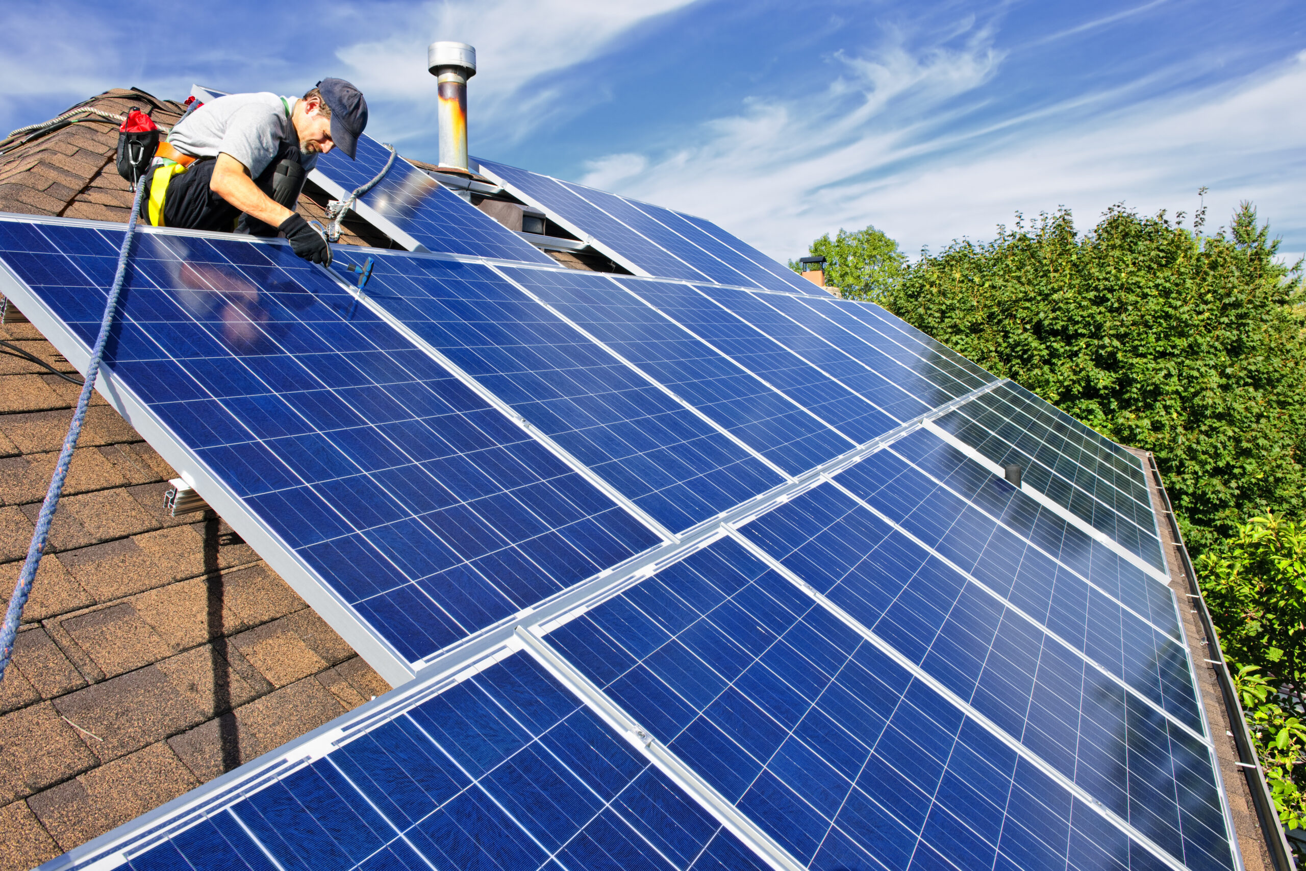 workers installing solar panel on a roof